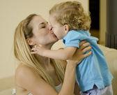 Vacker ung mamma kysser hennes söta son — Stockfoto