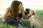 Young beautiful woman with her pug dog at the park — Stock Photo