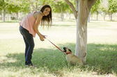 Cute young woman walking her dog at a park — Stock Photo