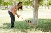 Leuke jonge vrouw lopen haar hond op een park — Stockfoto