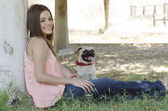 Cute young woman sitting next to a tree with her pug dog — Stock Photo