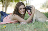 Cute young woman spending some time with her pug dog at the park — Stock Photo
