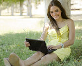 Young beautiful woman working on a laptop at the park — Stock fotografie