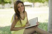Молодая красивая женщина, чтения и отдыха в парке — Стоковое фото