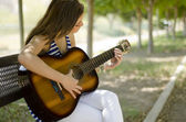 Cute young woman playing some music at the park — Stock Photo