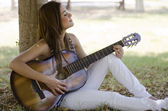 Cute young woman playing guitar at the park — Stock Photo