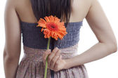 Young woman hiding a flower behind her back — Stock Photo