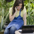 Young beautiful woman working on a laptop at the park — Stock Photo