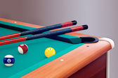 Green billiard table with balls and cues — Stock Photo
