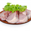 Fresh pork meat with lettuce leaves on brown plate isolated on w — Stock Photo #11527519