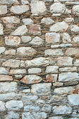 Traditional greek wall by rocks — Stock Photo