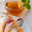 Croissant with jam and tea with a lemon - Stock Photo