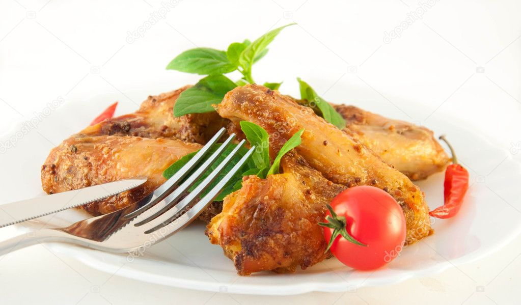 Chicken wings a grill with a tomato and a basil — Stock Photo #11445847