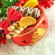 Christmas bag with gifts, cookies and fruit candy, a fur-tree branch — Stock Photo #11459840
