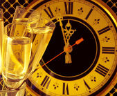 Christmas card. Glasses of champagne on New Year's Eve against an ancient wall clock — Stock Photo