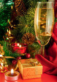 Tarjeta de Navidad. Champagne, una rama de un árbol de la piel y una vela sobre un fondo rojo — Foto de Stock