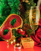 Christmas card. Champagne, a branch of a fur-tree, a candle and a carnival mask — Stock Photo