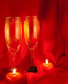 Celebratory table layout with red napkins and candles in the form of heart — Stock Photo