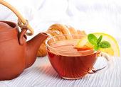 Xícara de chá perfumado fluir de um bule de cerâmica — Fotografia Stock