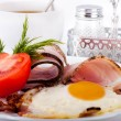 Royalty-Free Stock Photo: Fried eggs with bacon and tomatoes, a nourishing breakfast