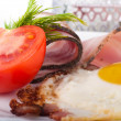 Stock Photo: Fried eggs with bacon and tomatoes, a nourishing breakfast