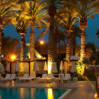 Stock Photo: Night swimming pool against the backdrop of palm trees and hotels