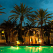 Stock Photo: Night swimming pool against backdrop of palm trees and hotels
