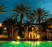 Night swimming pool against the backdrop of palm trees and hotels — Stock Photo