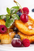 Pancakes with berries and mint on a white background — Stockfoto