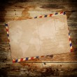 Vintage postcard with envelop on wooden background — Stock Photo