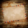 Stock Photo: Vintage postcard with envelop on wooden background