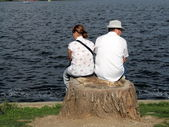 Man and woman sitting on the waterfront, Herastrau Gardens, Bucharest — Stock Photo