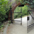 Classical design black wrought iron gate in a beautiful green garden - Stock Photo