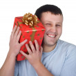 Happy young man with a red gift — Stock Photo