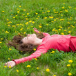 Smiling dreaming girl lying among dandelions — Stock Photo