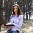 Stock Photo: Young businesswoman with laptop working outdoors
