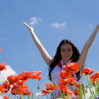 Girl rising up her hands at poppy field — Stock Photo