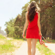 Girl in red dress walk barefoot on hot summer sand — Stock Photo #11387852