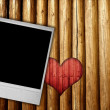 Photo frame on wood background with heart — Stock Photo #11387854