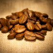 Coffee beans on sacking in warm soft light — Stock Photo