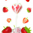 Many beautiful strawberries falling in milk - Stock Photo