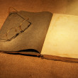 Stock Photo: Old book and glasses in ambient light