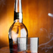 Glass and bottle of whiskey with smoke - Stock Photo