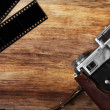 Old camera and blank film strip — Stock Photo