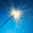 Sparkler on blue background — Stock Photo