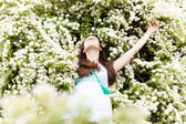 Beautiful smiling young woman relax in white summer flowers — Stock Photo