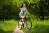 Happy girl over a bicycle on forest pathway — Zdjęcie stockowe