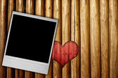 Photo frame on wood background with heart — Stock Photo