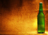 Beer bottle on sacking with copy-space — Stock Photo