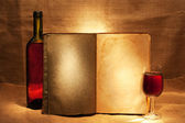 Wine and open book in a warm evening light — Stock Photo